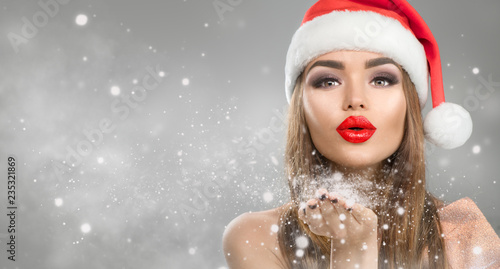 Christmas winter fashion girl on holiday blurred winter background. Beautiful New Year and Xmas holiday makeup. Beauty model woman in Santa's hat blowing snow in her hand © Subbotina Anna