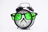 Cheerful alarm clock in green glasses on a light background.