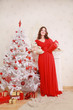 a nice woman in a long red evening dress shyly smiles near a white Christmas tree and a fireplace with gifts