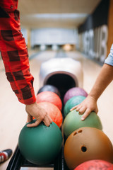 Two male bowlers takes balls from feeder