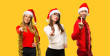 A group of people Blonde woman dressed up for christmas holidays showing and lifting a finger in sign of the best on yellow background - 235369672