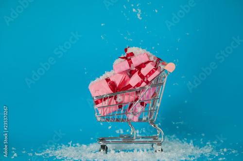 Sprzedaż świąteczna. Kupowanie prezentów na nowy rok, koncepcja. Koszyk jest pełen pudełek