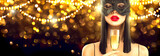 Christmas and New Year holiday celebration. Beauty glamour woman celebrating with champagne, wearing carnival mask, drinking sparkling wine over holiday glowing background. Widescreen - 235371425