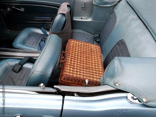 Picknickkoffer aus braunem Korbgeflecht auf dem Rücksitz eines amerikanischen Cabriolet mit blauem Kunstleder bei den Golden Oldies in Wettenberg Krofdorf-Gleiberg bei Gießen in Mittelhessen