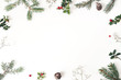 Christmas floral frame, decorative border. Winter composition of red cranberry branches, baby's breath flowers, spruce tree branches and larch cones on white table. Festive background. Flat lay, top