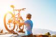 Leinwandbild Motiv Mountain biker man take of his bike from the car roof evening sunset image