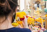 A woman make ceremonial offerings from floral garlands at the Erawan Shrine in Bangkok, Thailand.