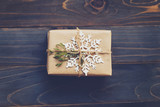 String or twine tied in a bow on kraft paper. Above gift box on wood with space. - 235388807