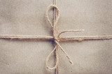 String or twine tied in a bow on brown kraft paper texture. - 235388815