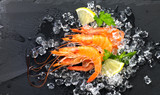 Shrimps. Fresh prawns on a black background. Seafood on crashed ice with herbs. Healthy food, cooking - 235462465