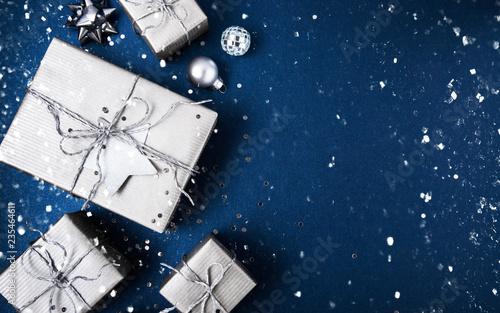 Merry Christmas and Happy Holidays greeting card, frame, banner. New Year. Noel. Silver Christmas gifts, ornaments on blue background top view. Winter holiday xmas theme. Flat lay. - 235464611