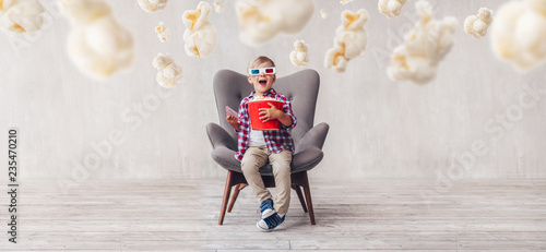 Leinwandbild Motiv Surprised kid with popcorn in 3d glasses