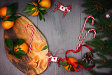 Christmas concept - board with tangerines, candy canes and decorations in the form of horses