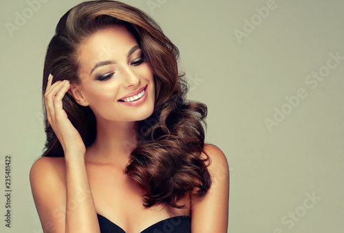 Leinwanddruck Bild Beautiful model girl with long wavy and shiny hair . Brunette woman with curly hairstyle
