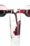 Cranberry and black currant syrup pouring into water glass on white background