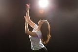 People and dancing concept - Young beautiful sporty woman dancing jazz funk on a black studio background