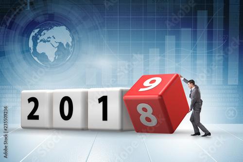 Leinwanddruck Bild Businessman employee rotating cube to reveal number 2019