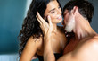 Leinwanddruck Bild - Sexy young couple kissing and playing in bedroom