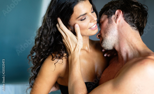 Leinwanddruck Bild Sexy young couple kissing and playing in bedroom