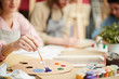 One of students taking violet color from wooden palette while painting at lesson