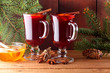 Leinwandbild Motiv Mulled wine and Christmas tree branches on wooden boards. Christmas mulled wine, cinnamon sticks, anise and honey. Alcoholic drink of wine, fruit and honey. Festive drink on wooden boards