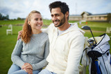 Cheerful young couple in casualwear sitting on green field for golf playing and chatting