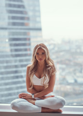 Beautiful fitness model meditating in a living apartment.