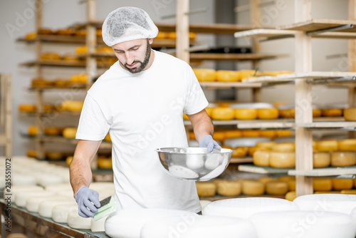 Man rubing cheese wheels with wax at the cheese manufacturing with shelves full of cheese on the background