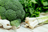 Broccoli, parsley and leek on the wooden table with reusable canvas bag. Less plastic grocery concept. Closeup food photo of local market products  - 235551291