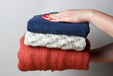 Female hands with a red manicure holding a stack of knitted woolen things, front view, close-up