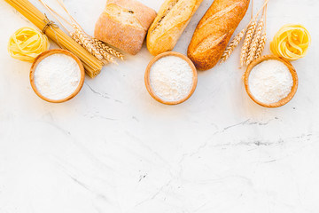 Homemade fresh bread and pasta near flour in bowl and wheat ears on white stone background top view copy space
