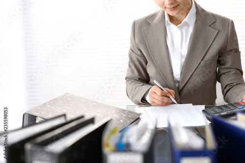 Bookkeeper woman or financial inspector  making report, calculating or checking balance, close-up. Business portrait. Copy space area for audit or tax concepts - 235598053