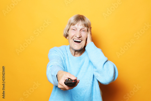 Leinwandbild Motiv lifestyle and people concept: grandma is holding a TV remote over yellow background