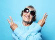 Funny old lady wearing blue sweater, hat and sunglasses showing victory sign.