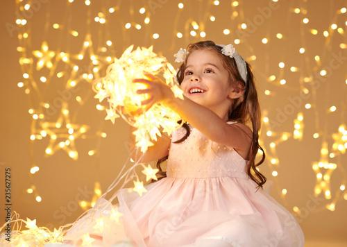 Leinwandbild Motiv girl child is posing with christmas lights, yellow background, pink dress