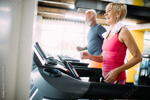 Foto Murales Senior people running in machine treadmill at fitness gym club
