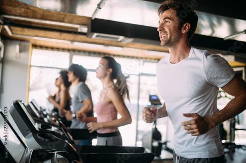 Leinwanddruck Bild Young people running on a treadmill in health club.
