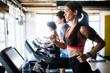 Leinwandbild Motiv Young people running on a treadmill in health club.