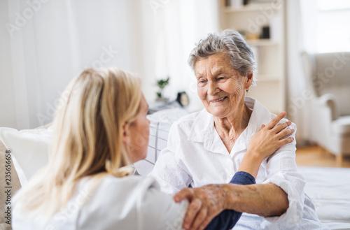 Leinwandbild Motiv A health visitor talking to a sick senior woman sitting on bed at home.