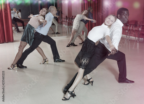 fototapeta na ścianę Adult couples dancing active dance together in modern studio
