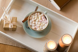 holidays and still life concept - hot chocolate with marshmallow, christmas gift and candles on table - 235672053