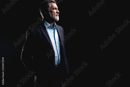 Leinwanddruck Bild Handsome mature business man isolated on black background
