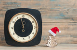vintage wall clock with Santa hat on wooden table - 235673835