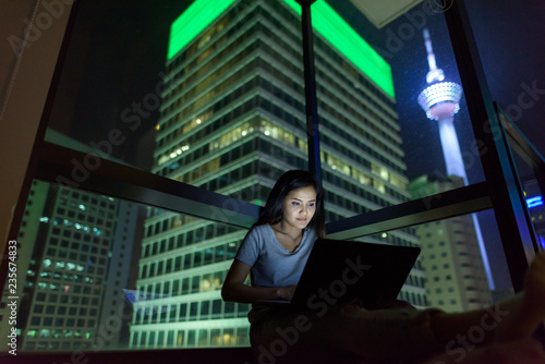 Young beautiful Asian woman using laptop against glass window wi - 235674833