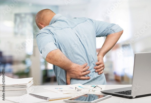 Leinwanddruck Bild Business man with back pain an office