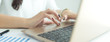 Close up hands of young business woman using laptop computer for working at desk with documents. Banner with copyspace for your text.