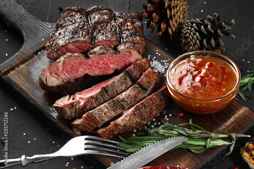 Sliced grilled medium rare beef steak served on wooden board Barbecue, bbq meat beef tenderloin. - 235712266