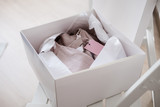 White opened box with wrapping paper and pink linen cloth and label. Copyspace for text - 235714480