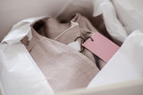 White opened box with wrapping paper and pink linen cloth and label. Copyspace for text - 235714487