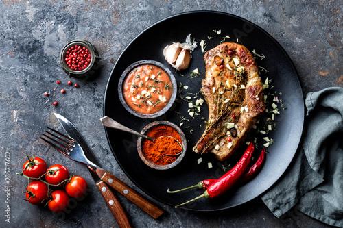 fried pork steak with garlic and thyme in dark plate on dark background - 235717602